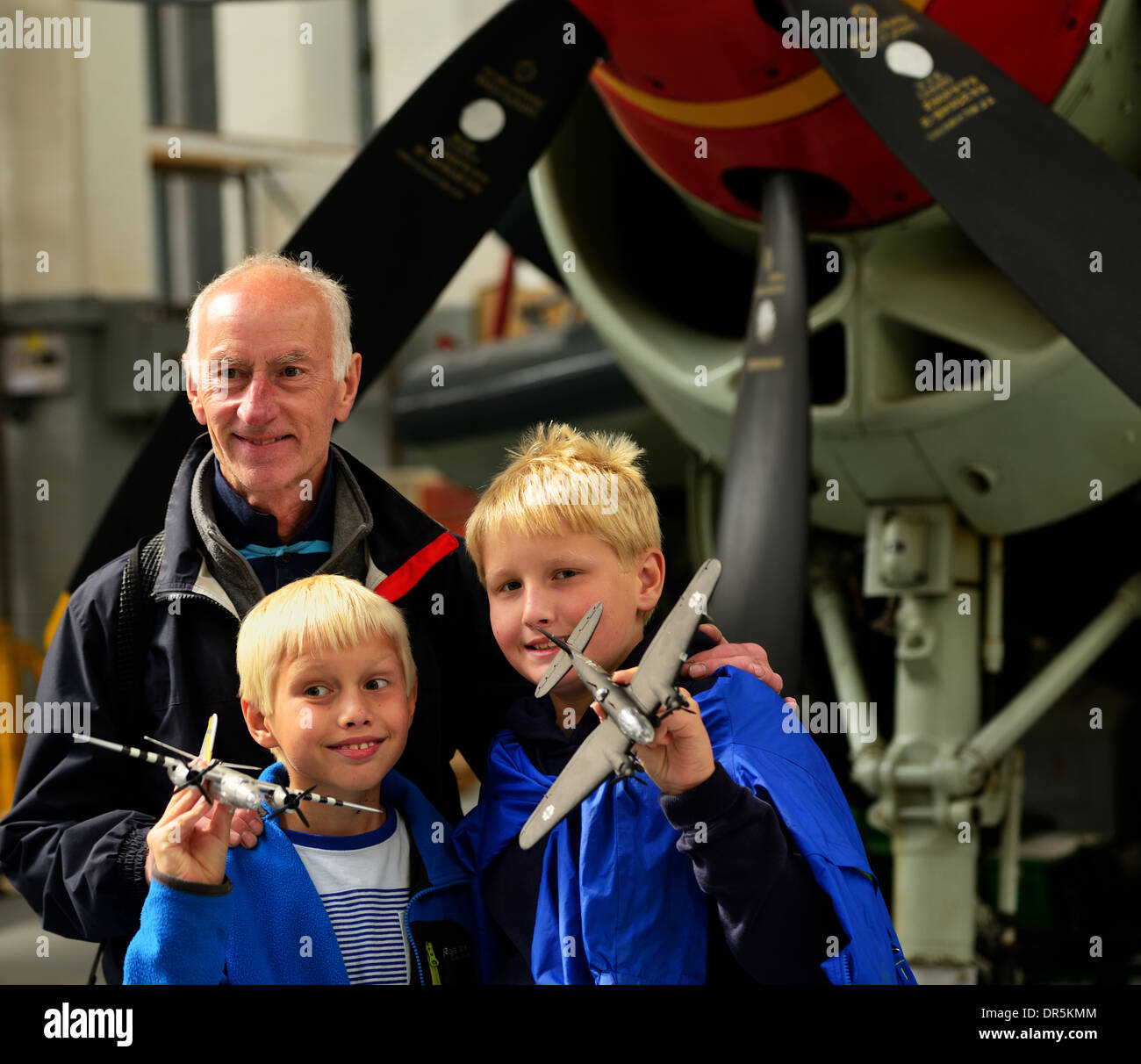 Father with two young blonde boys with model planes in an aircraft hanger at Duxford air museum - Stock Image