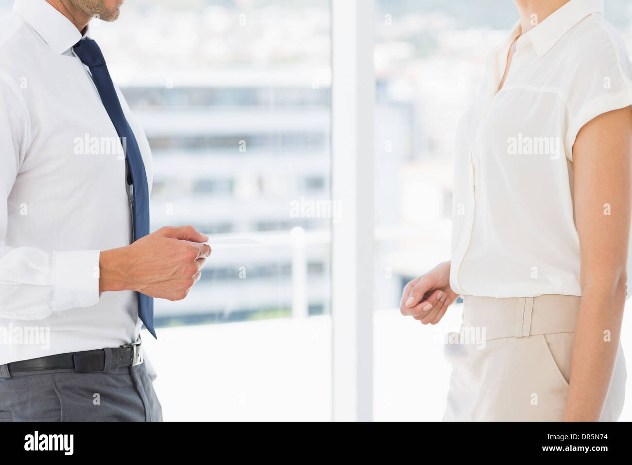 Mid section of executives exchanging business card - Stock Image