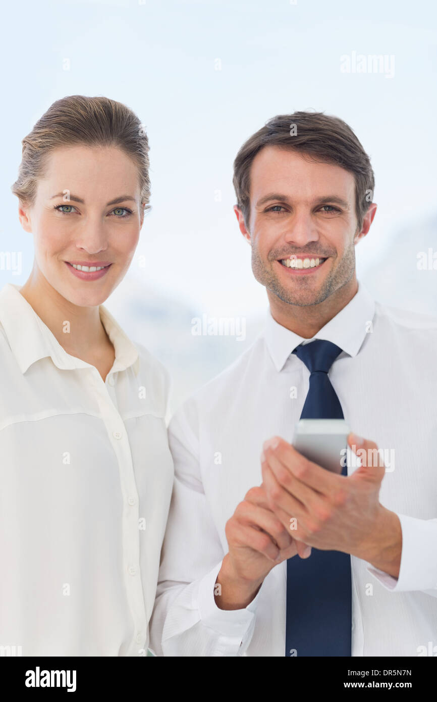 Smartly dressed colleagues with a mobile phone - Stock Image