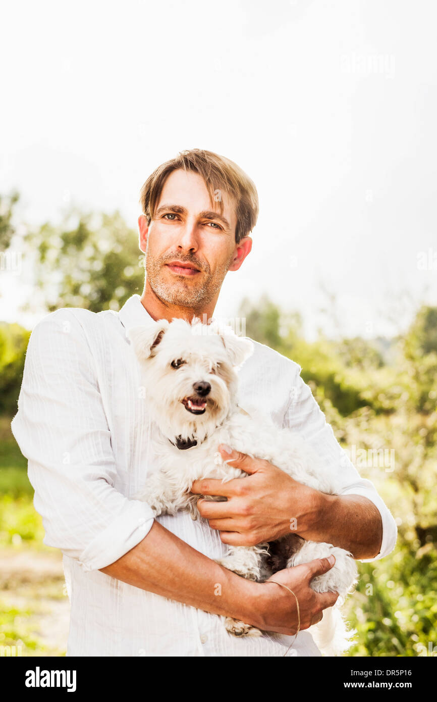 Man with dog in his arms outdoors, Bavaria, Germany - Stock Image