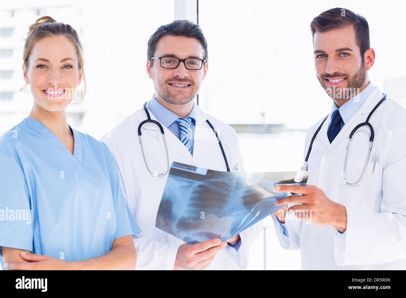 Portrait of doctors with x-ray report at medical office - Stock Image