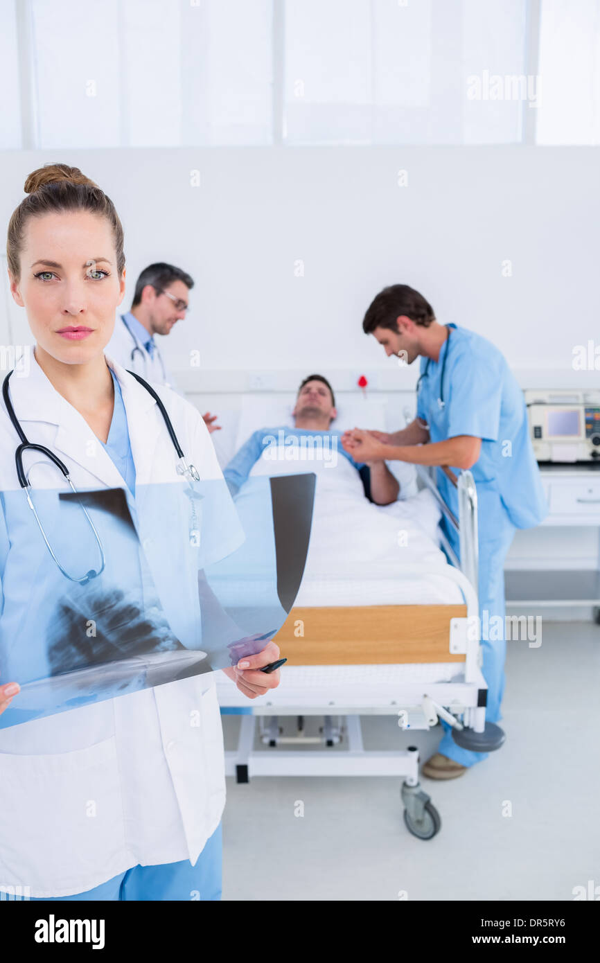Doctor holding x-ray with colleagues and patient in hospital - Stock Image