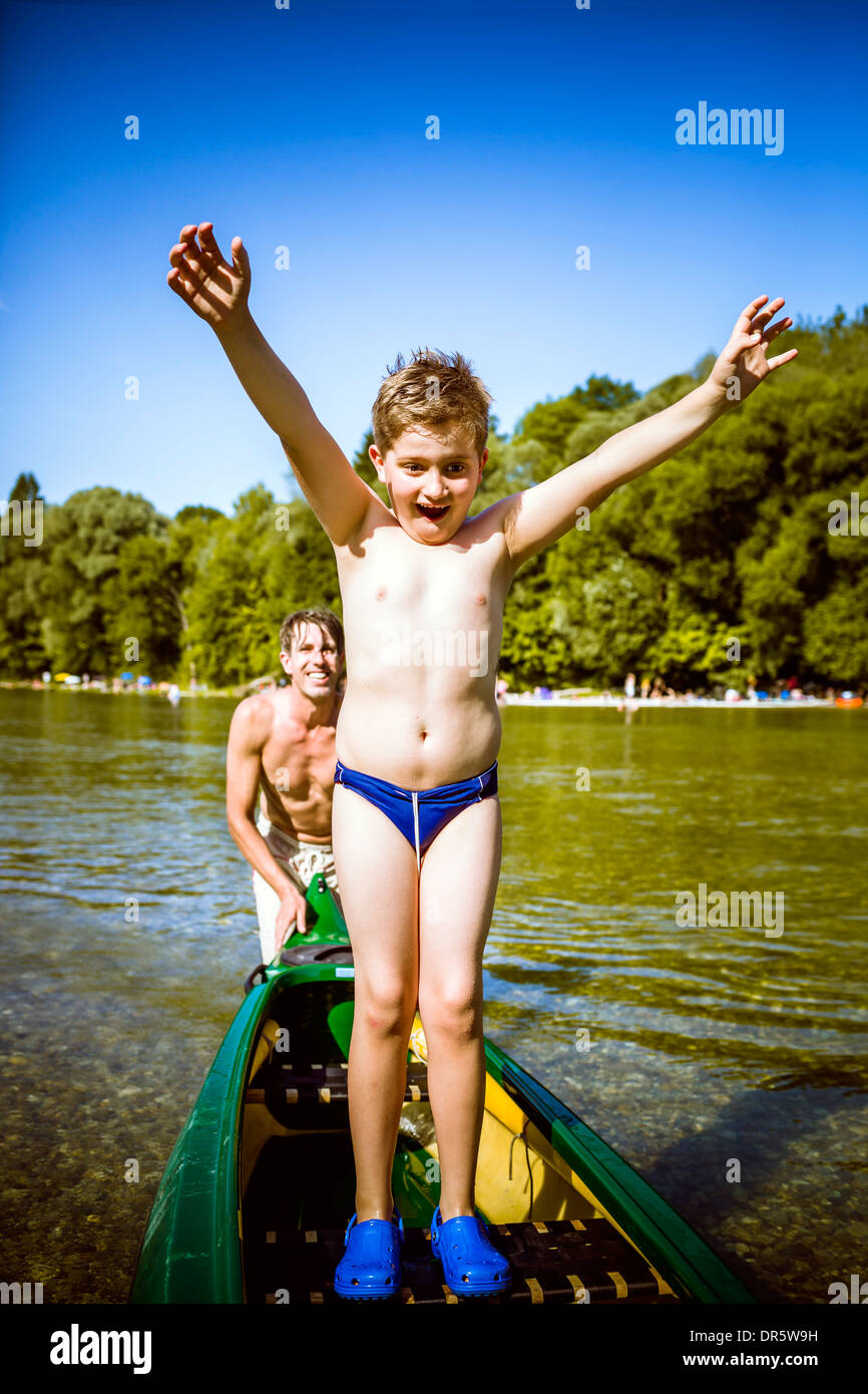 Boy in bathing trunks in a canoe, arms raised, Bavaria, Germany Stock Photo