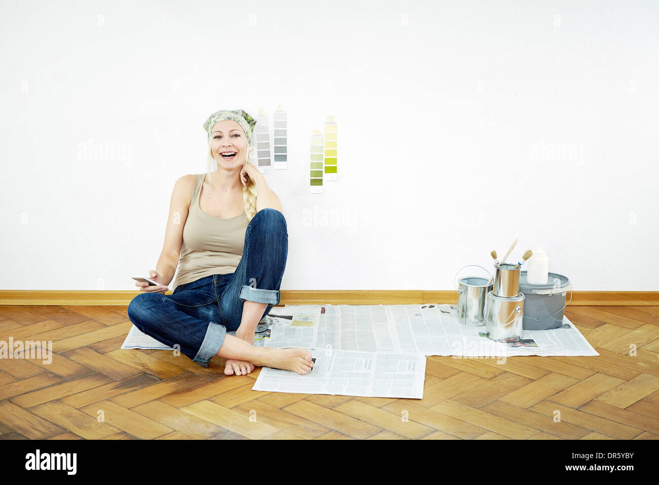 Woman sits on parquet floor, color samples on the wall, Munich, Bavaria, GermanyStock Photo