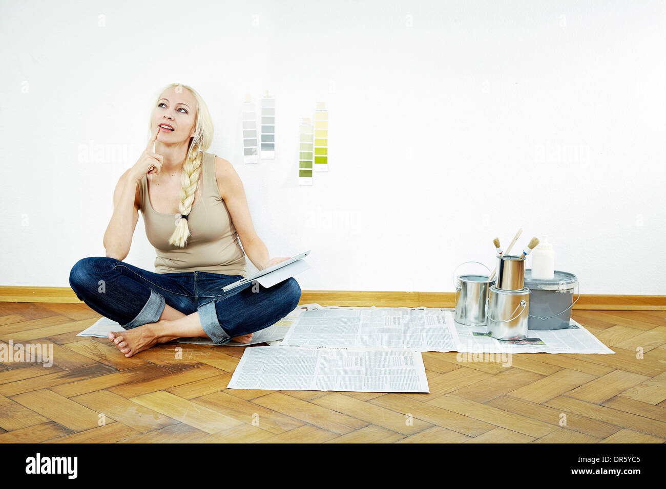Young woman sits on parquet floor, color samples on the wall, Munich, Bavaria, Germany Stock Photo