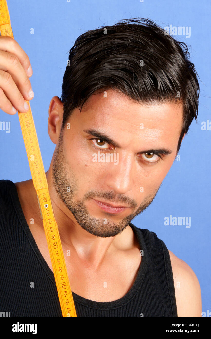 Carpenter worker holding a metric wood ruler over a blue background. - Stock Image