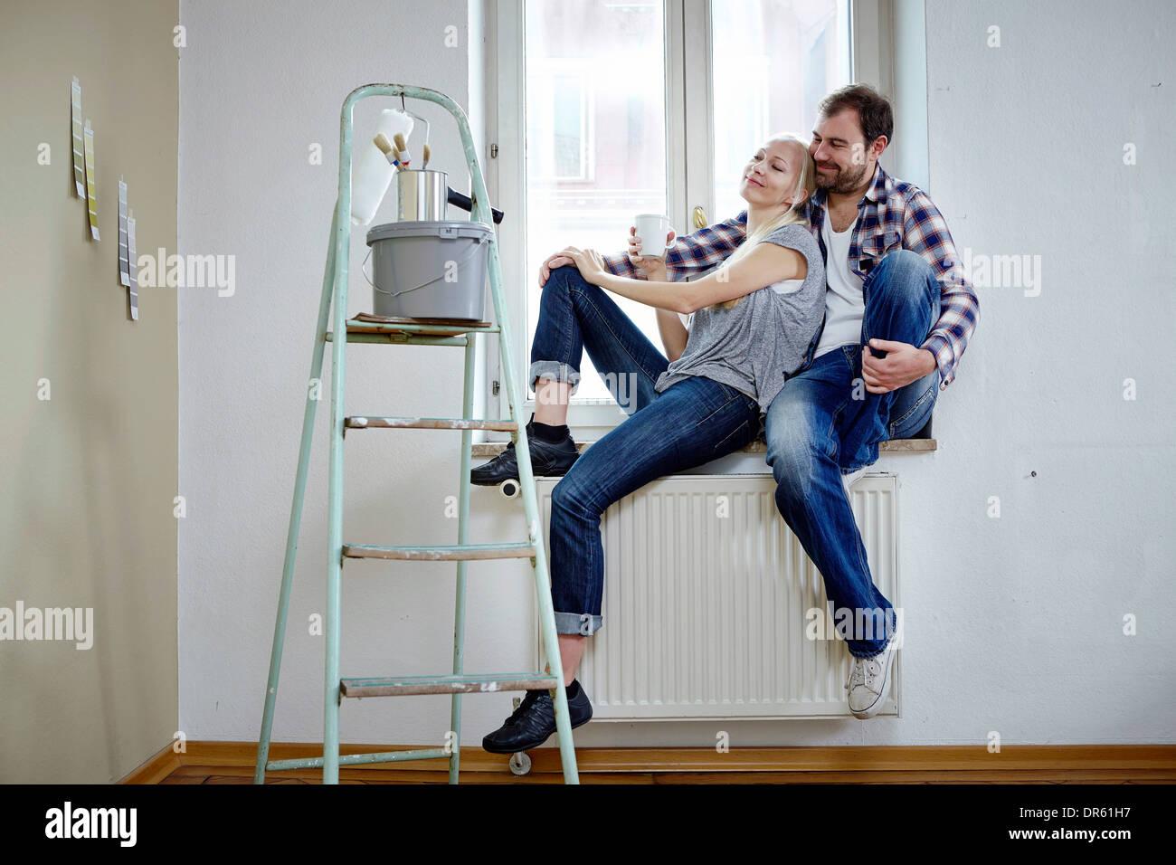 Home improvement, happy couple taking a break, Munich, Bavaria, Germany Stock Photo