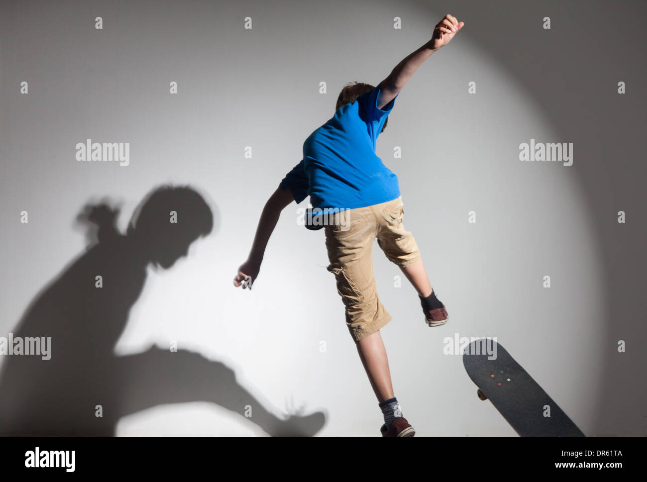 boy leaping with skateboard and shadow - Stock Image