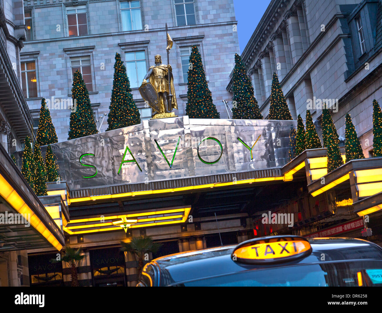 Exterior view of luxury Five-Star Savoy Hotel entrance at Christmas with London taxi for hire in foreground The Strand London - Stock Image