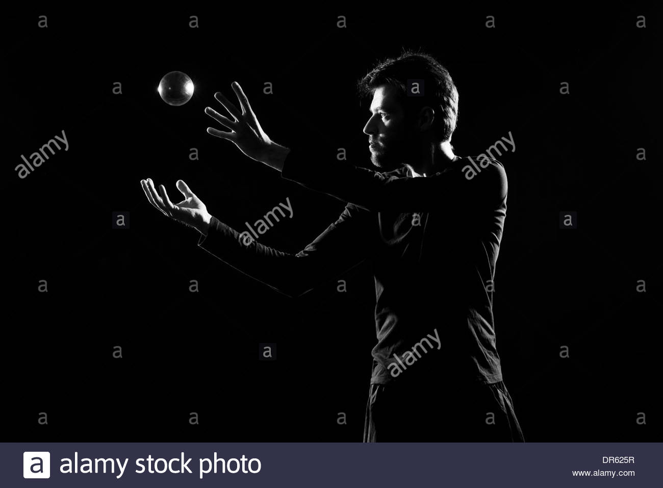 Man juggling with crystal ball before black background - Stock Image