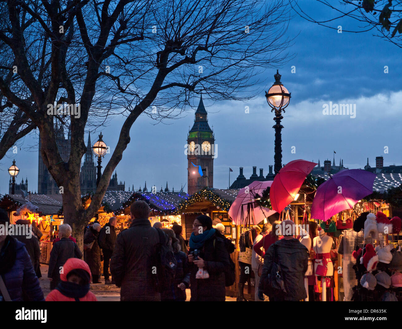 LONDON CHRISTMAS MARKET SHOPPERS LIGHTS South Bank Christmas market stalls and shoppers with Houses of Parliament behind at dusk London UK - Stock Image