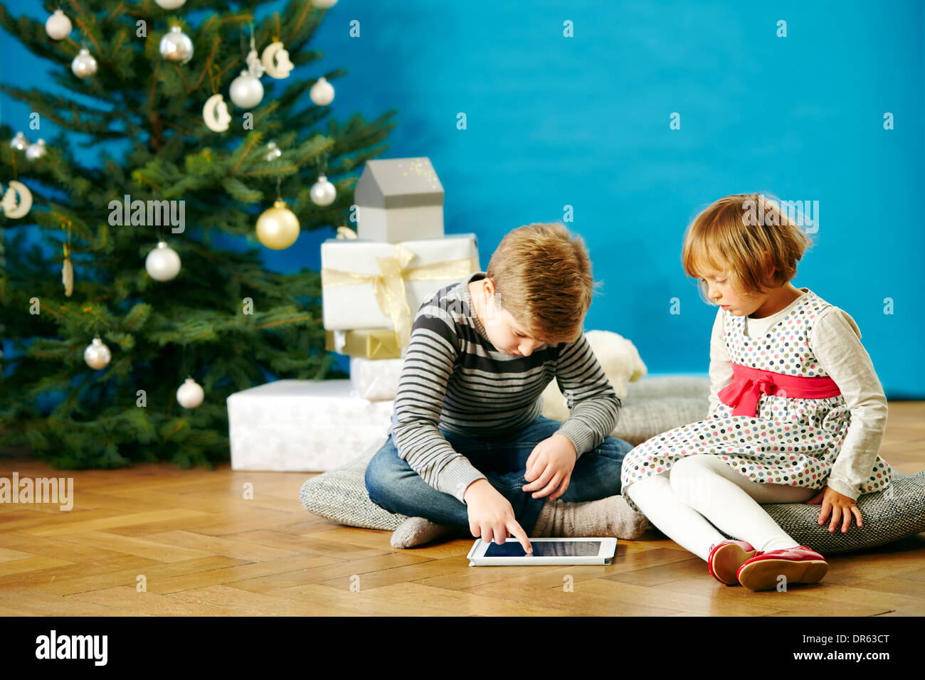Children playing with digital tablet on Christmas Eve, Munich, Bavaria, Germany - Stock Image