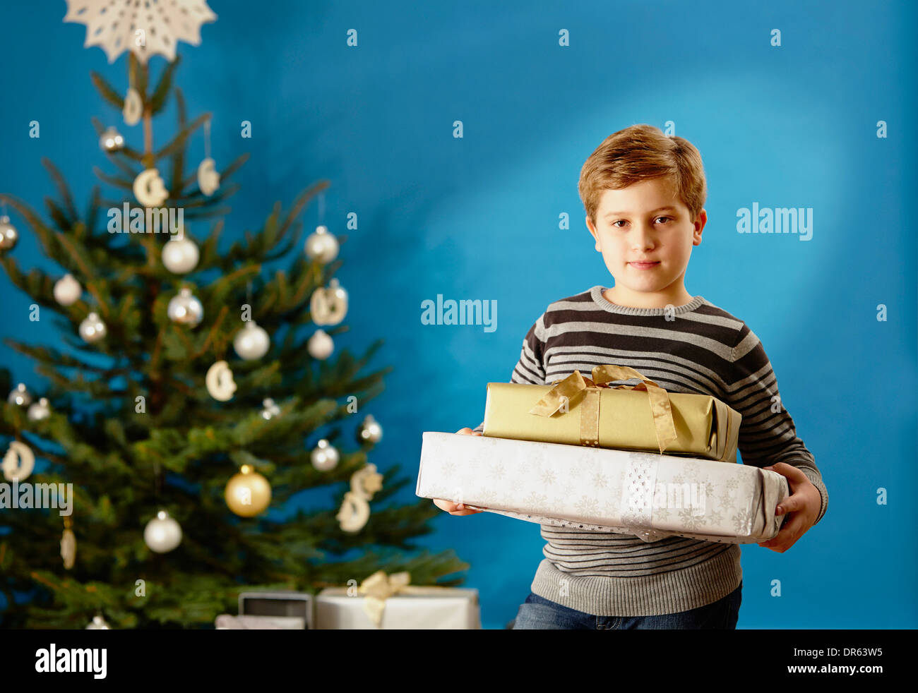 Little boy holding Christmas presents, Munich, Bavaria, Germany - Stock Image