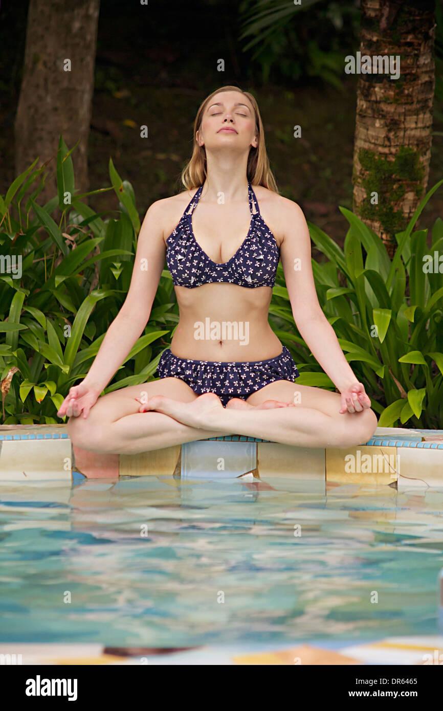 Young woman in yoga pose sits at swimming pool, Sepilok, Borneo,  Malaysia - Stock Image
