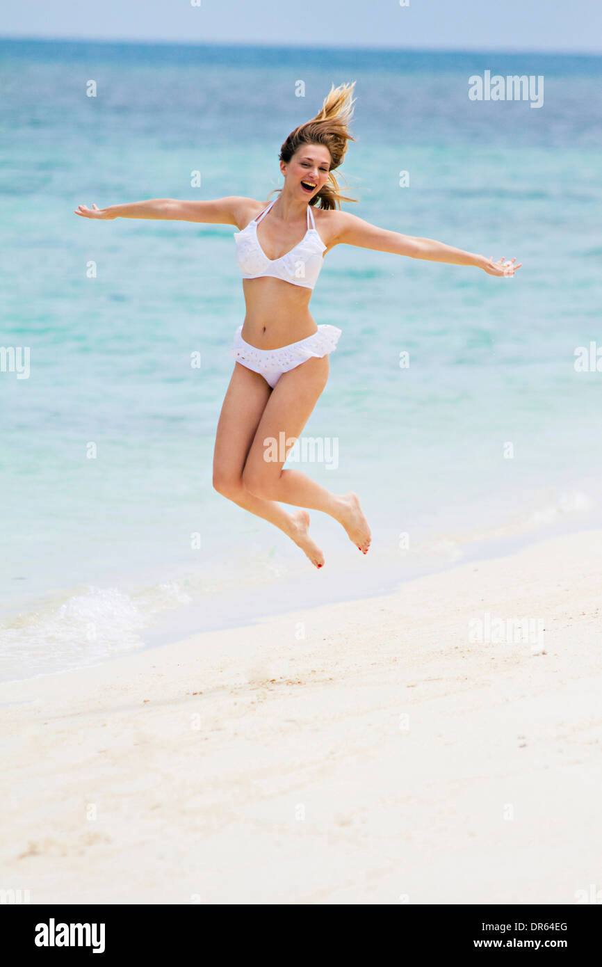 Young woman in bikini jumping on beach, Lankayan Island, Borneo, Malaysia - Stock Image