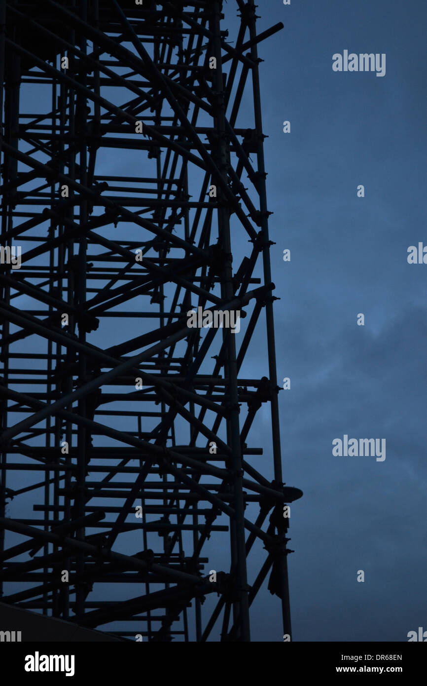 silhouette of scaffolding against stormy looking sky - Stock Image