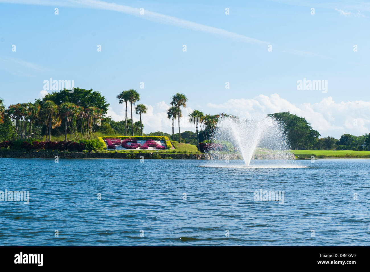 USA Florida PGA National Golf Course Palm Beach Gardens lake water feature fountain blue sky trees lawn flowers Stock Photo