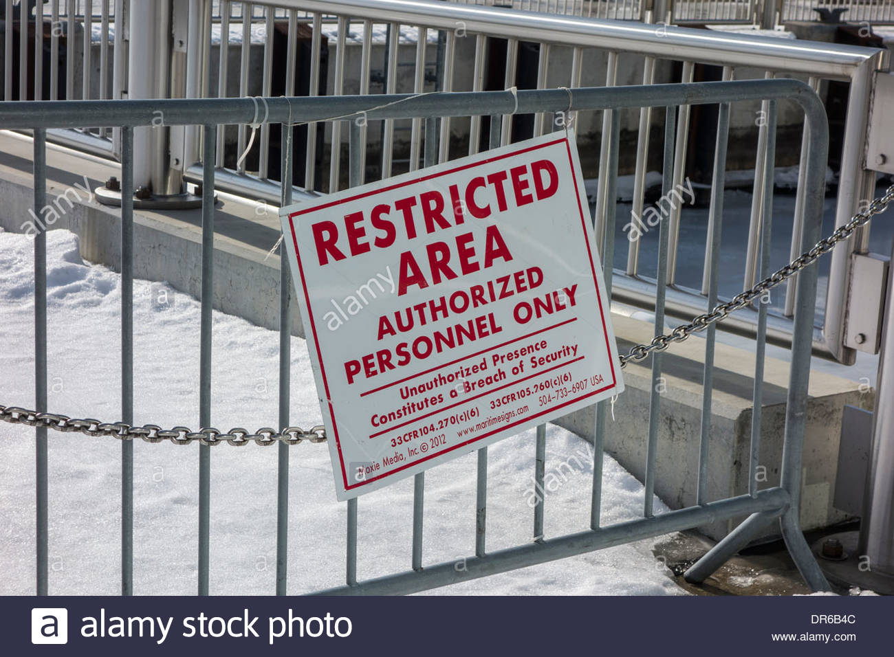 Restricted area sign on a metal barrier near to the river and the Port of Detroit - Stock Image