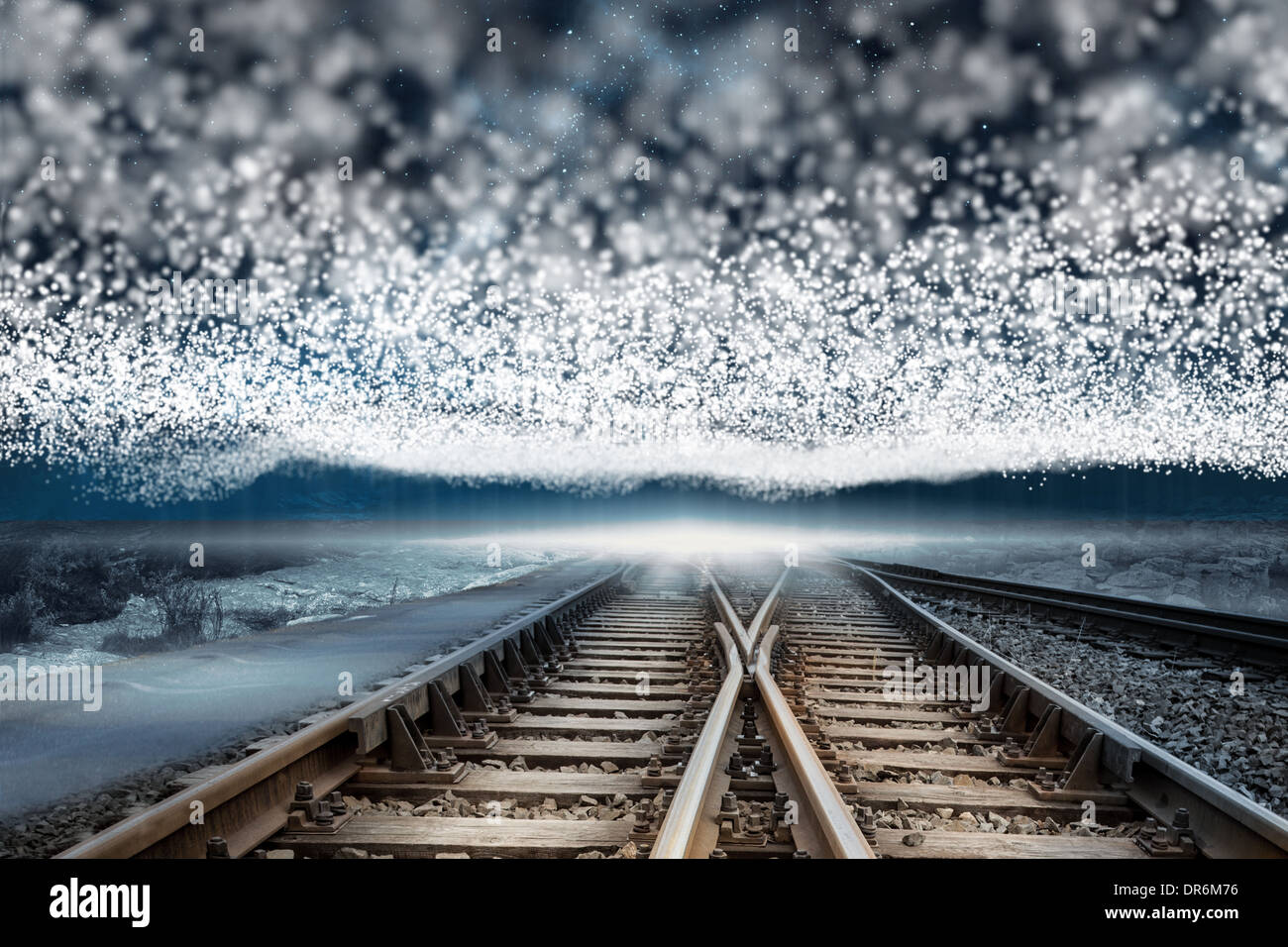 Train tracks under blanket of bright stars - Stock Image