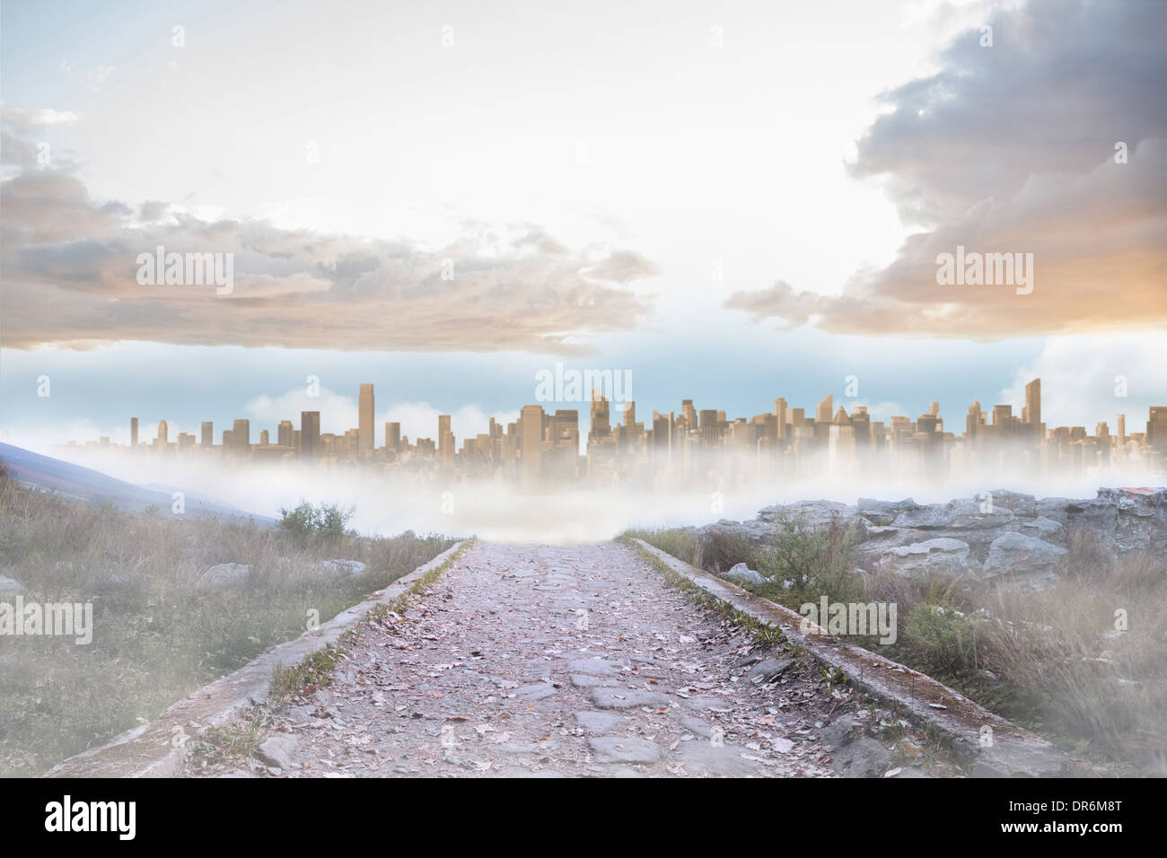 Rocky path leading to large urban sprawl - Stock Image