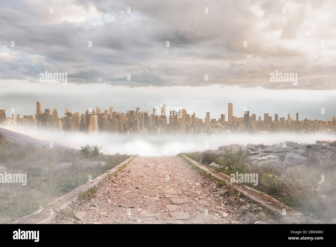 Stony path leading to large urban sprawl - Stock Image