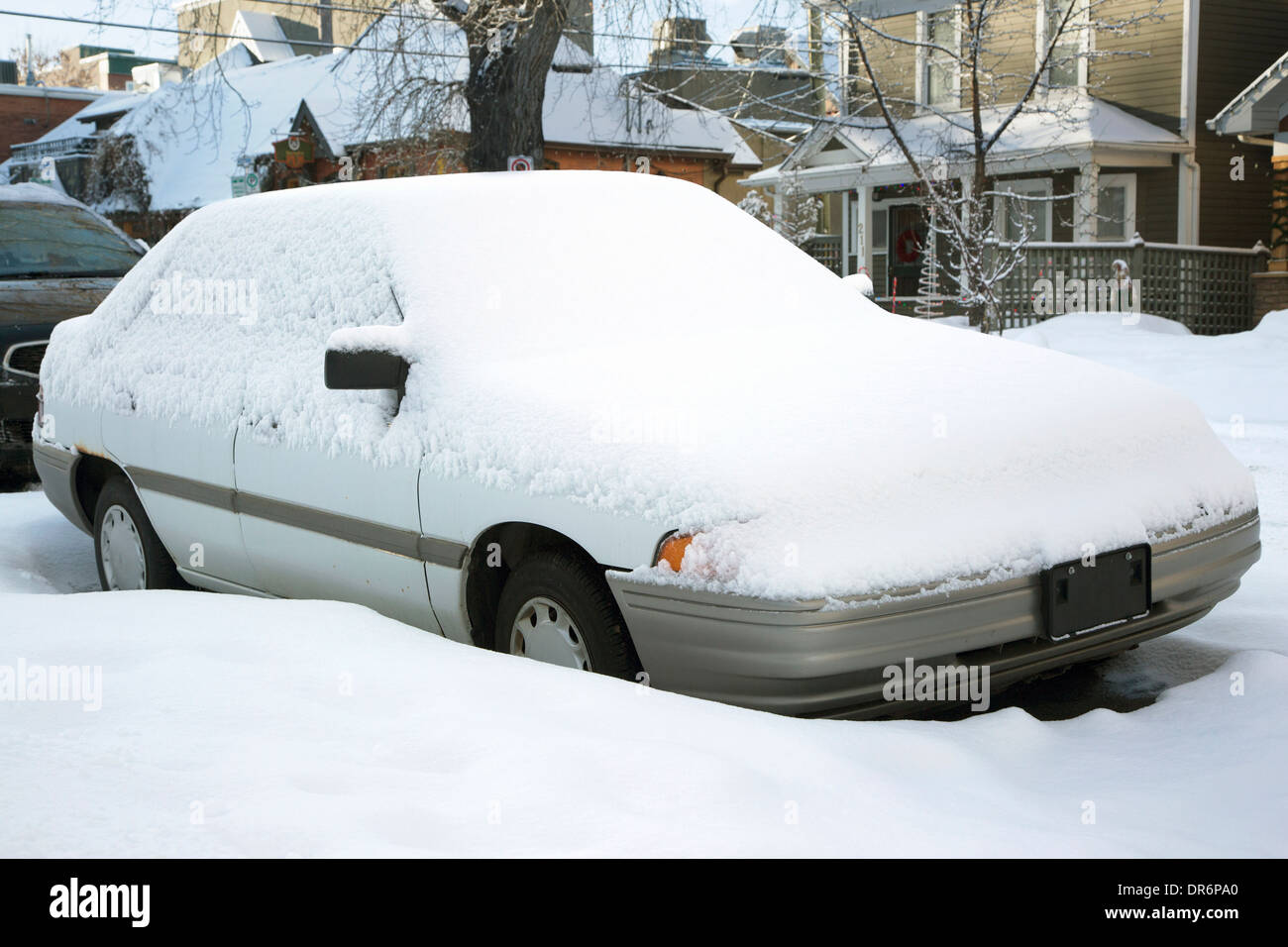 Car covered in snow on residential street - Stock Image
