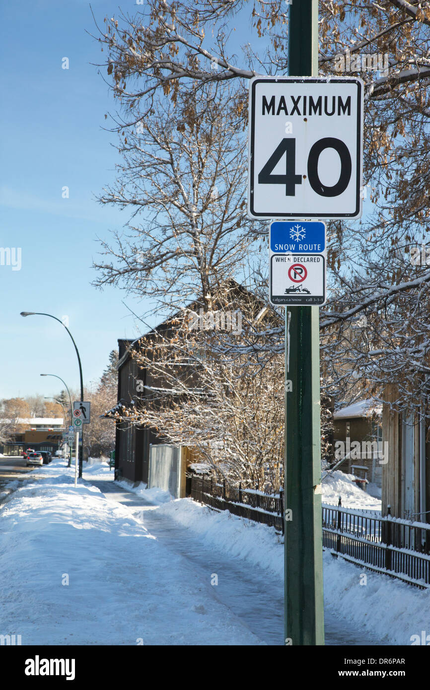 Street signs with speed limit of 40 km per hour and no-parking tow-away zone when the street is designated as a snow route. - Stock Image