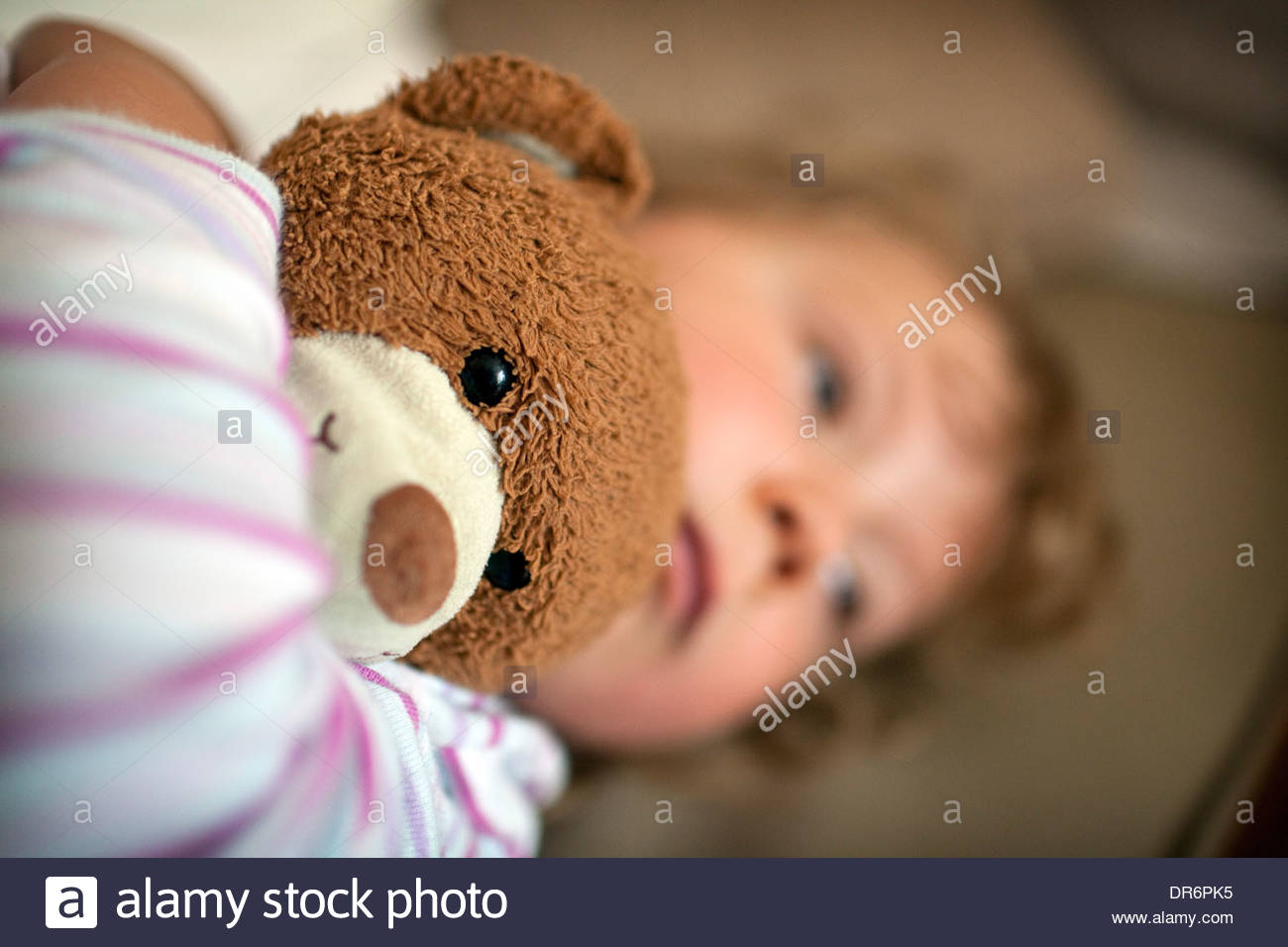 Girl holding a teddy bear and crying - Stock Image