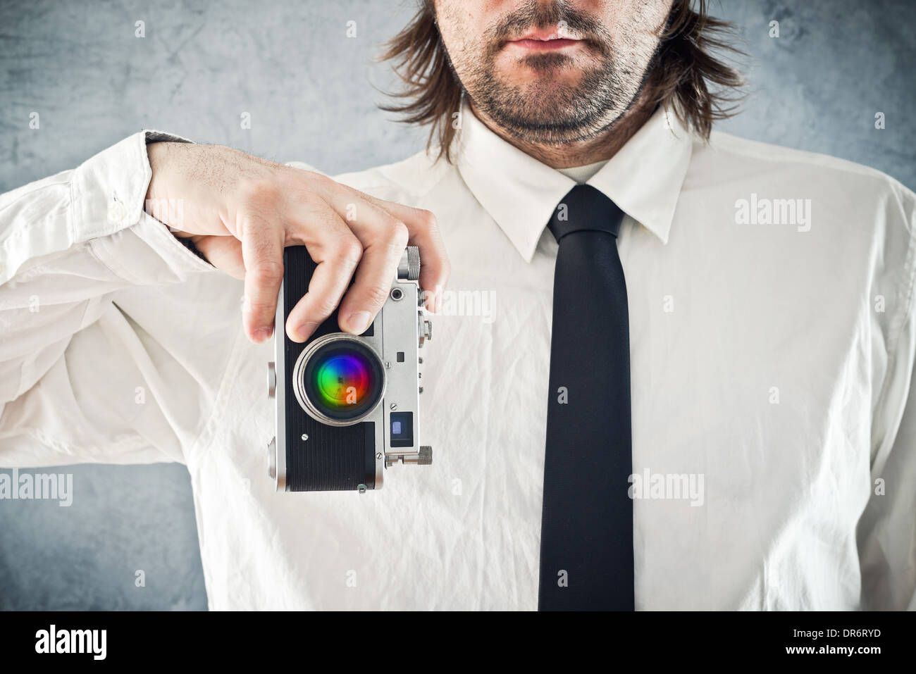 Businessman taking picture with retro style photo camera - Stock Image