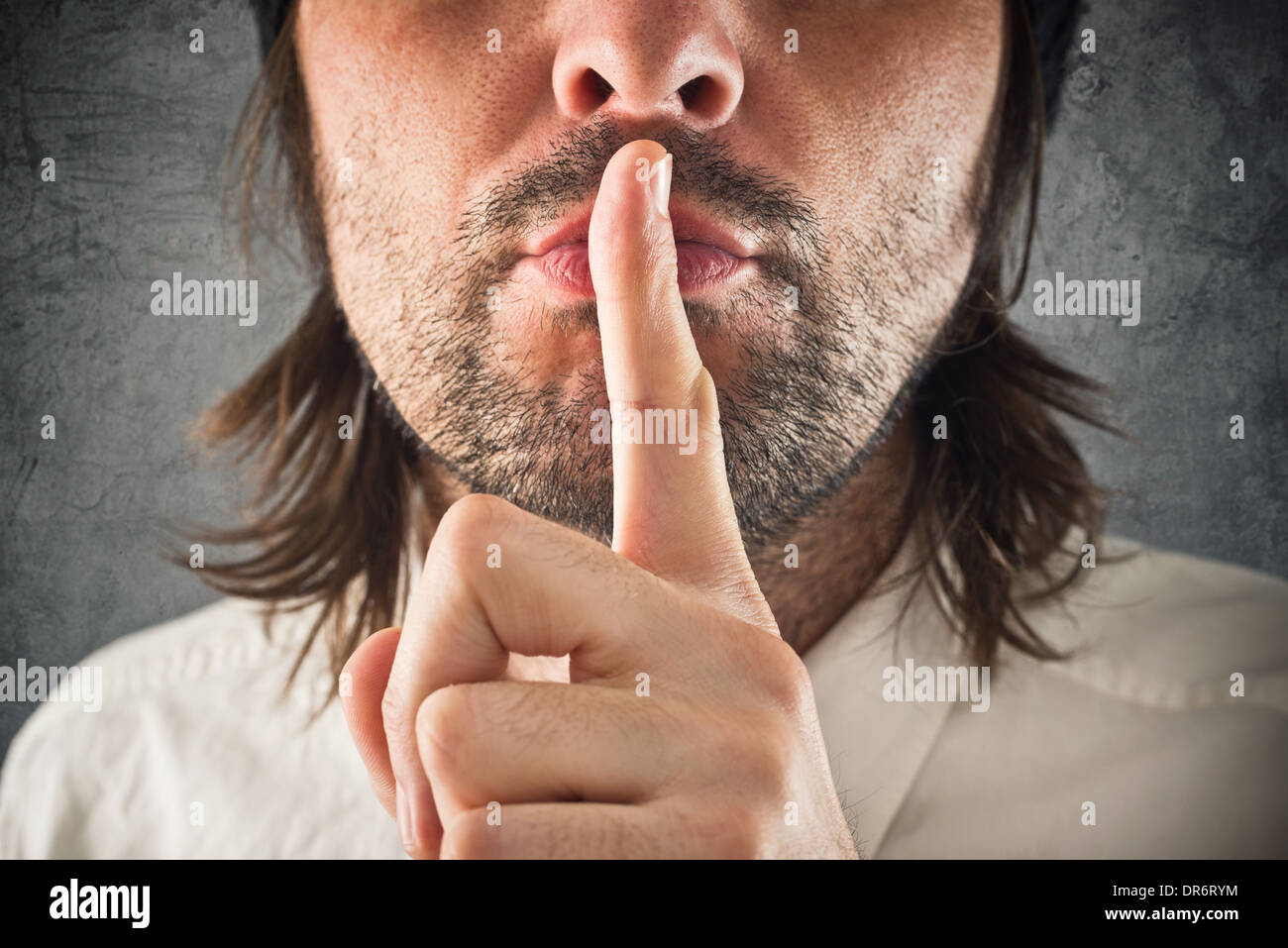 Businessman making hush gesture, finger on mouth for silence. - Stock Image