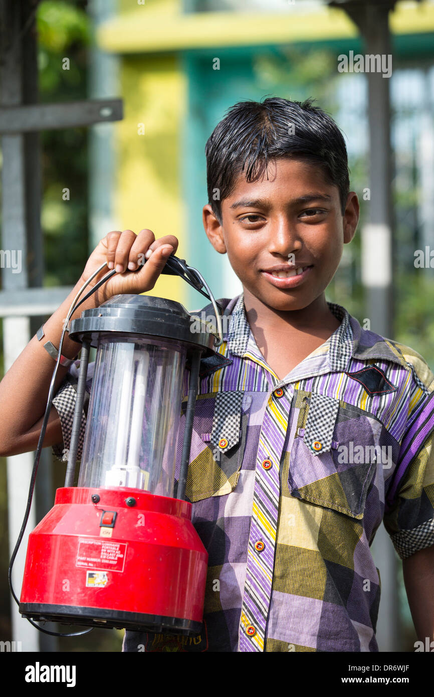 A WWF project to supply renewable electricity to a remote island in the Sunderbans, a low lying area of the Ganges Delta in Eastern India, that is very vulnerable to sea level rise. Prior to this project the subsistence farmers had no access to electricity. This shot shows a boy holding a solar lantern, charged from the solar panels. - Stock Image