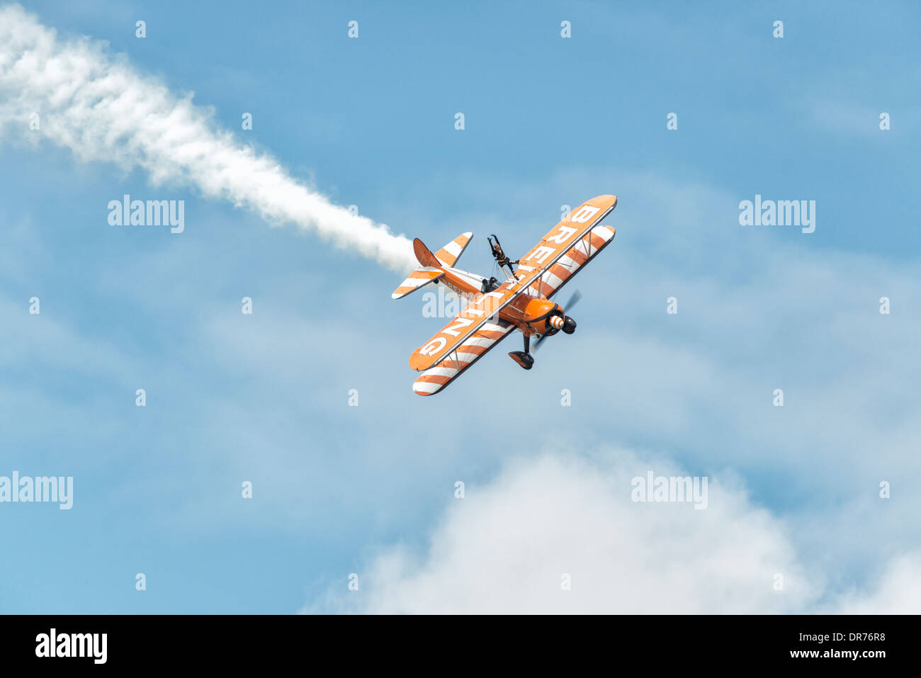 A Boeing Stearman Biplane from the AeroSuperBatics Breitling Wingwalking Team dives out of the sky at the RAF Fairford RIAT - Stock Image