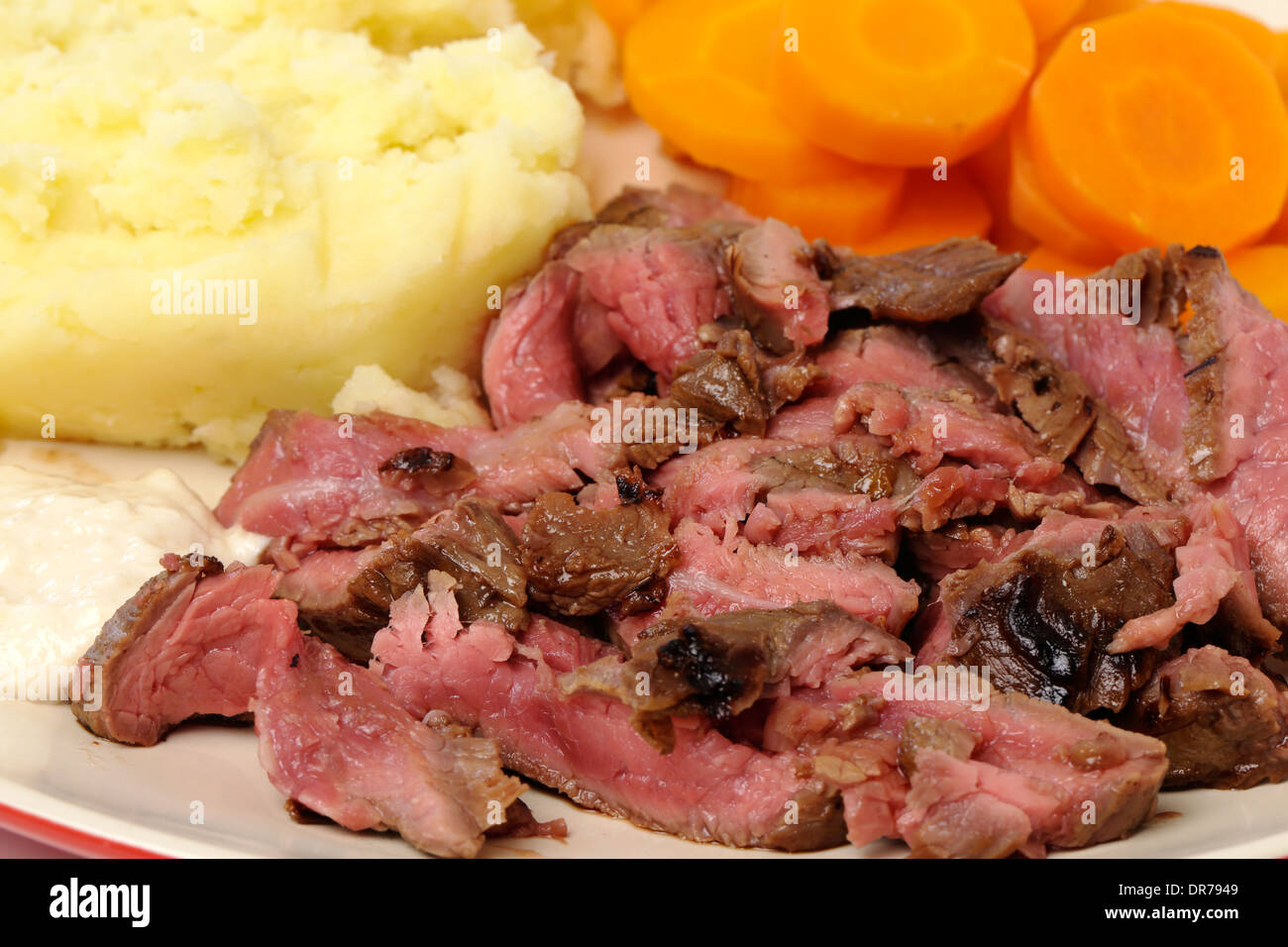 'London broil' marinaded flank of beef steak grilled and sliced thinly, then served with  potato,  carrots and horseradish sauce - Stock Image