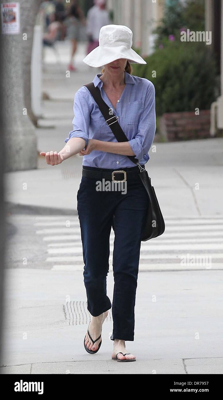 Marcia Cross wearing a large sun hat and Havaianas flip