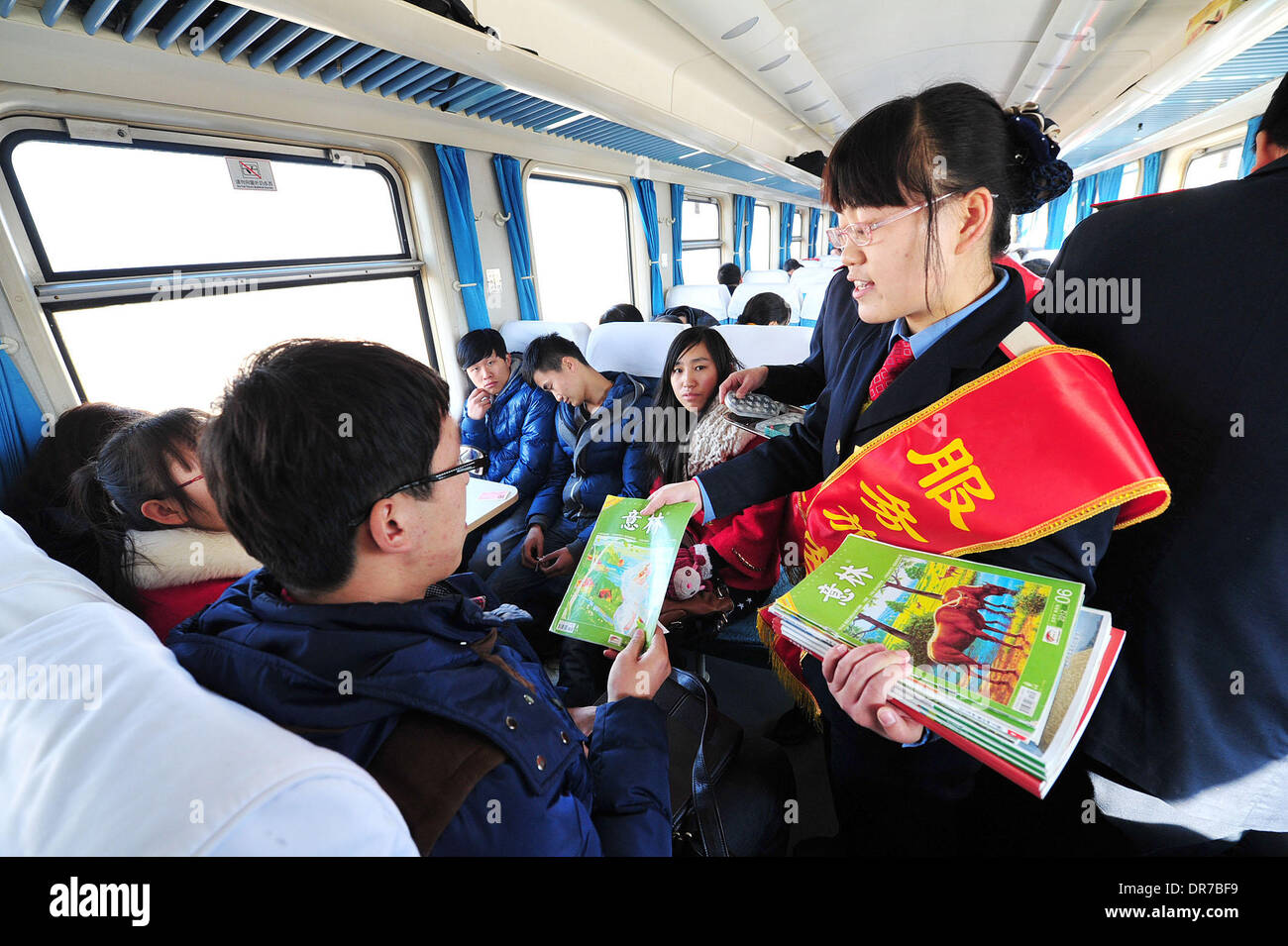 Yinchuan. 21st Jan, 2014. A steward distributes free books and magazines to  passengers