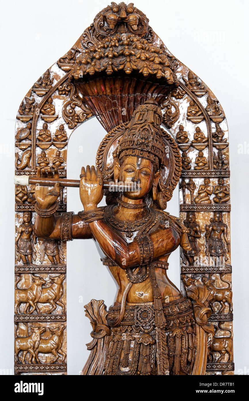 Ornate wooden carved krishna statue.  Worshiped hindu Indian deity - Stock Image