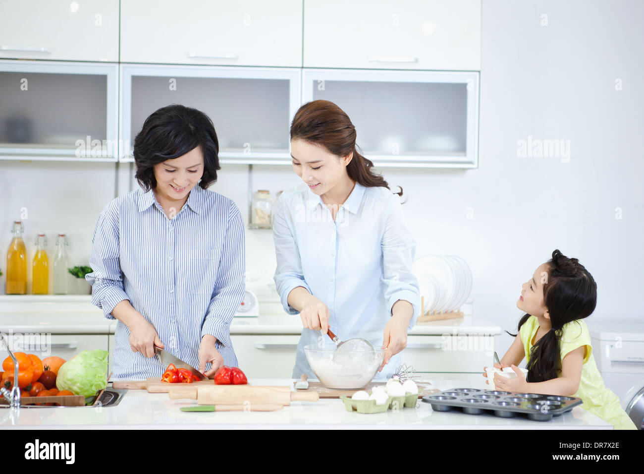 two women cooking in the kitchen while a child watching Stock Photo ...