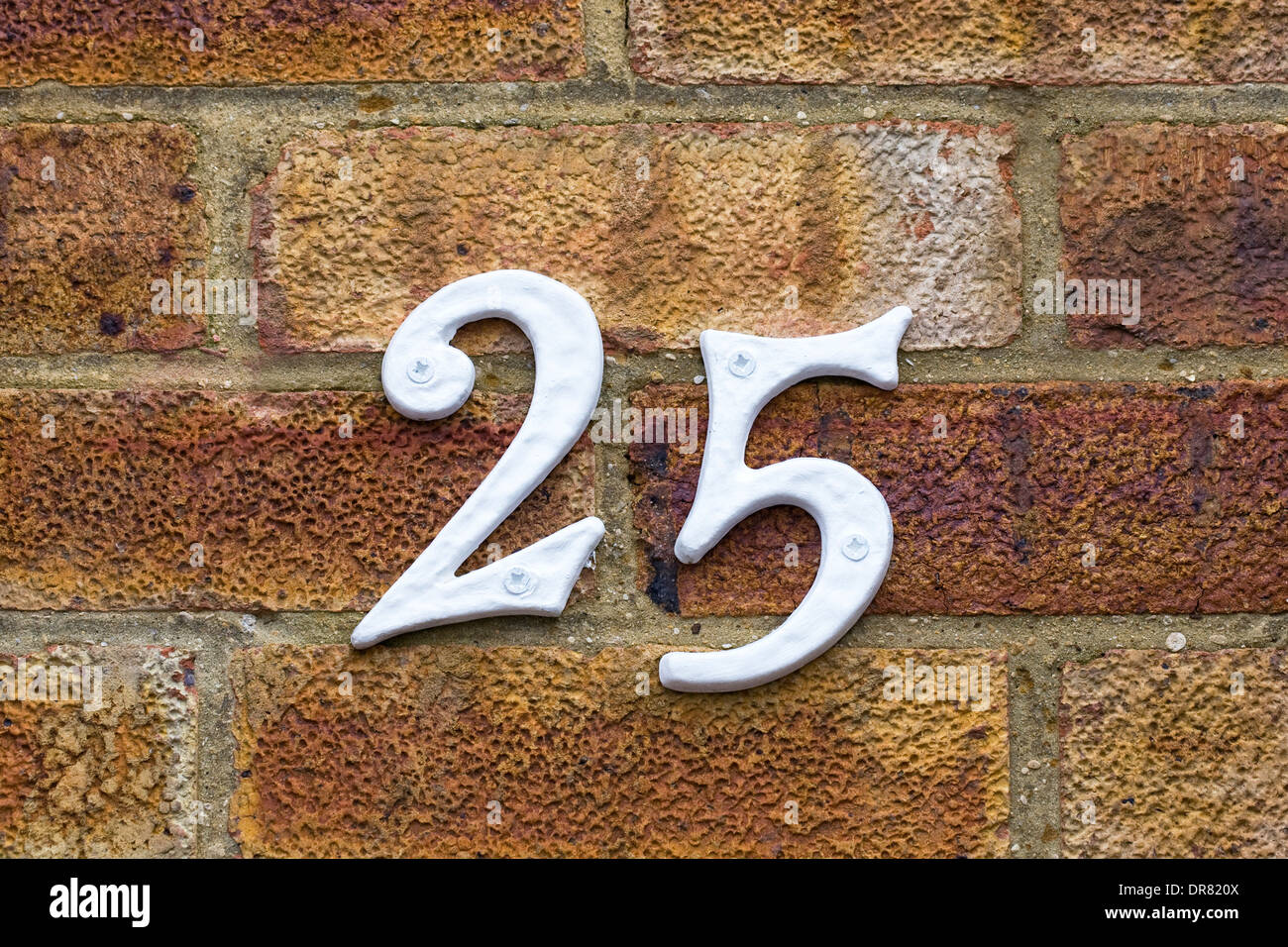 The number 25 attached to a brick wall. - Stock Image