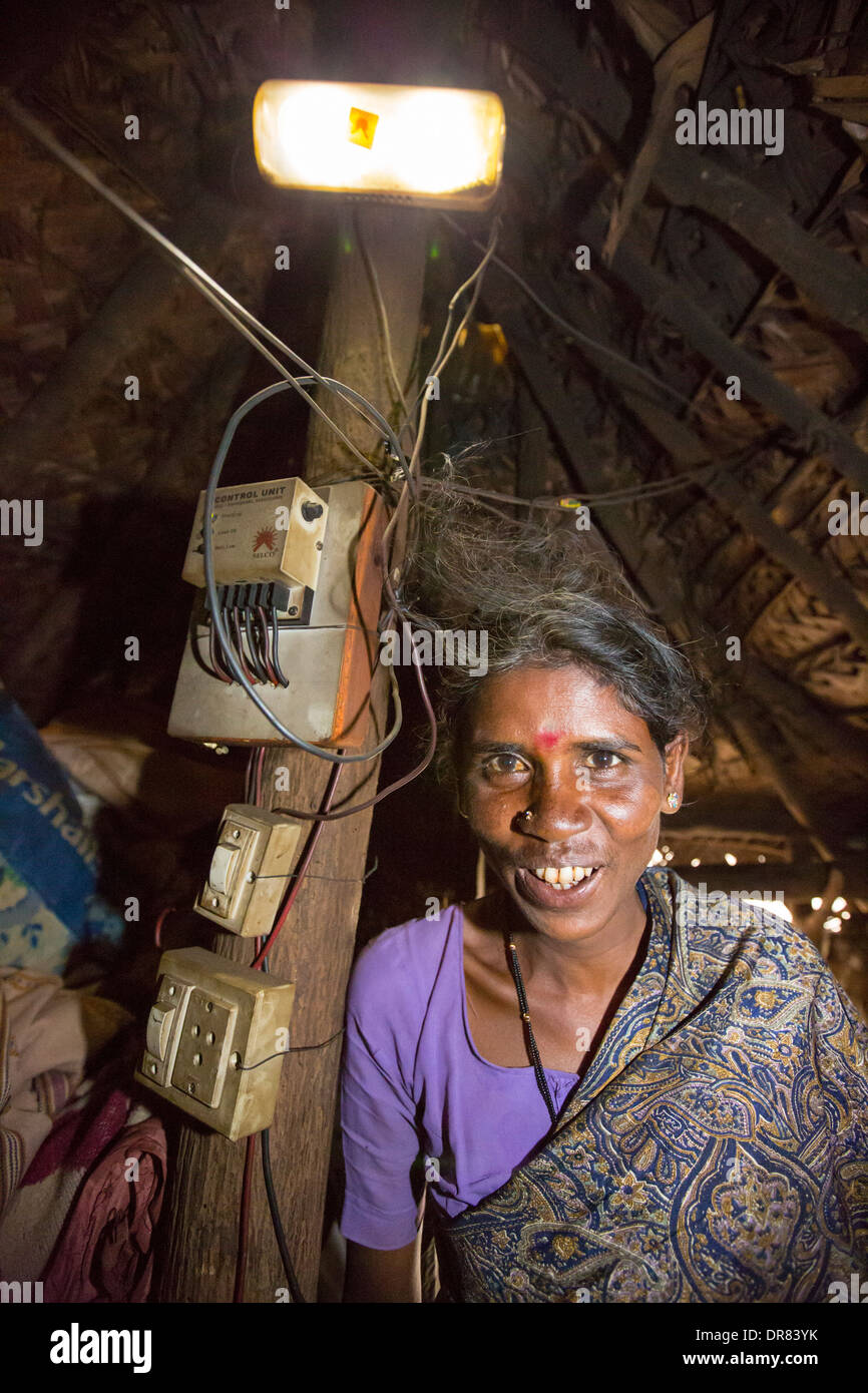 An untouchable woman in her hut, illuminated by an electric light, powered by an A4 sized solar panel, that charges a battery, and enables her to have light. The prrject was sponsored by the Rotary club. Before the installation of the solar panels, the houses would be lit by kerosene lamps. Over 1 million women and children die every year in india from inhaling kerosene fumes. - Stock Image