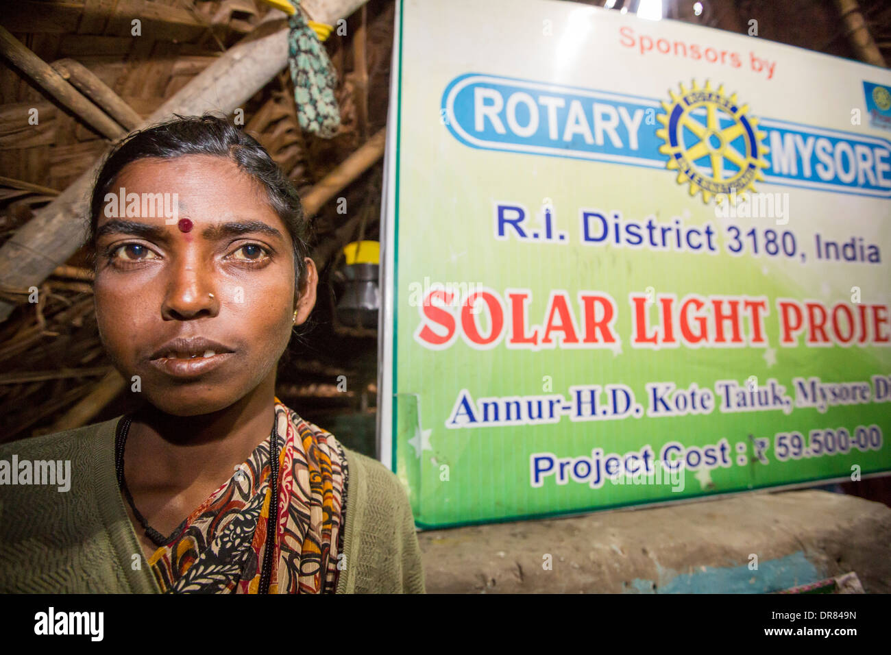 An untouchable woman in her hut, illuminated by an electric light, powered by an A4 sized solar panel, that charges a battery, - Stock Image
