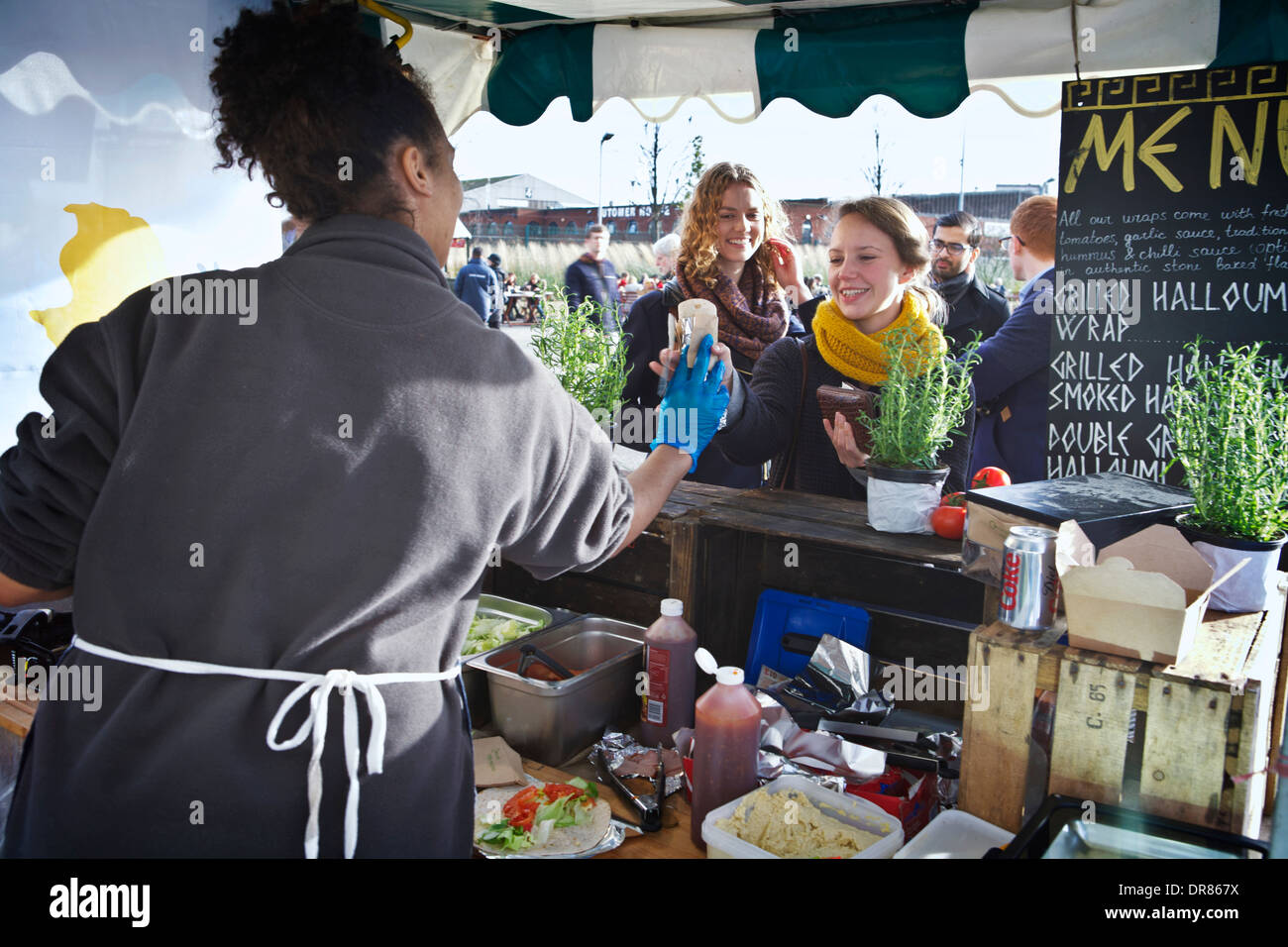 London market food stall at Canary Wharf. Vendor preparing & selling Greek food Halloumi wraps to queuing customers. Street food London. - Stock Image