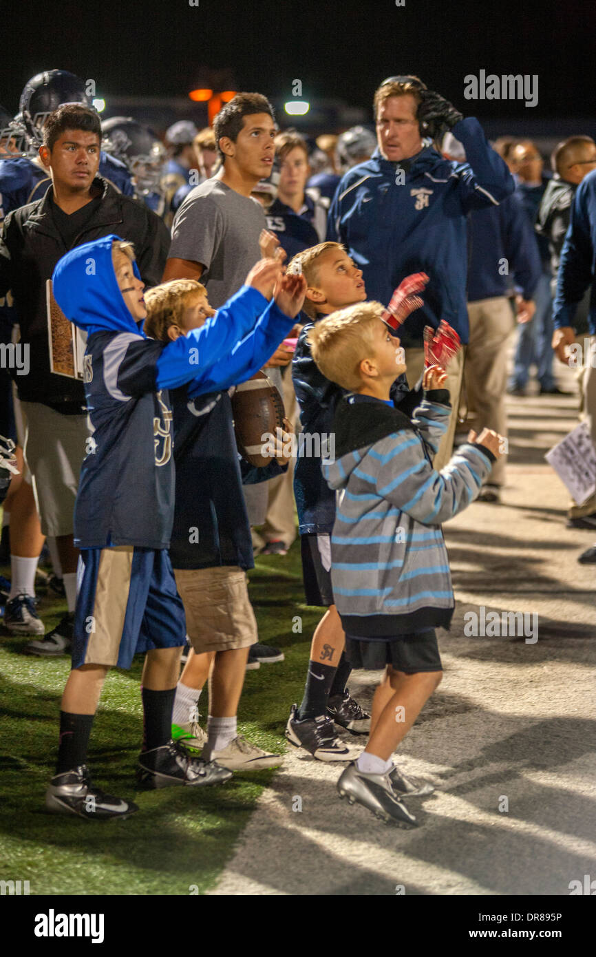Goal boys on the sidelines reach out to catch a stray ball during a night football game in San Juan Capistrano, CA. - Stock Image