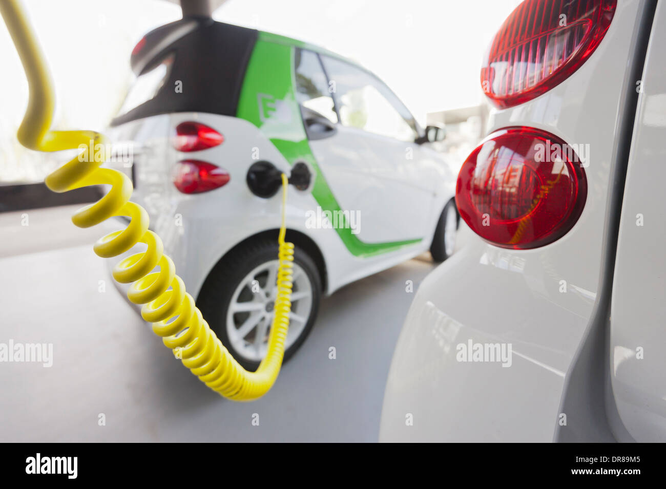 Electric vehicle charging at charge station - Stock Image