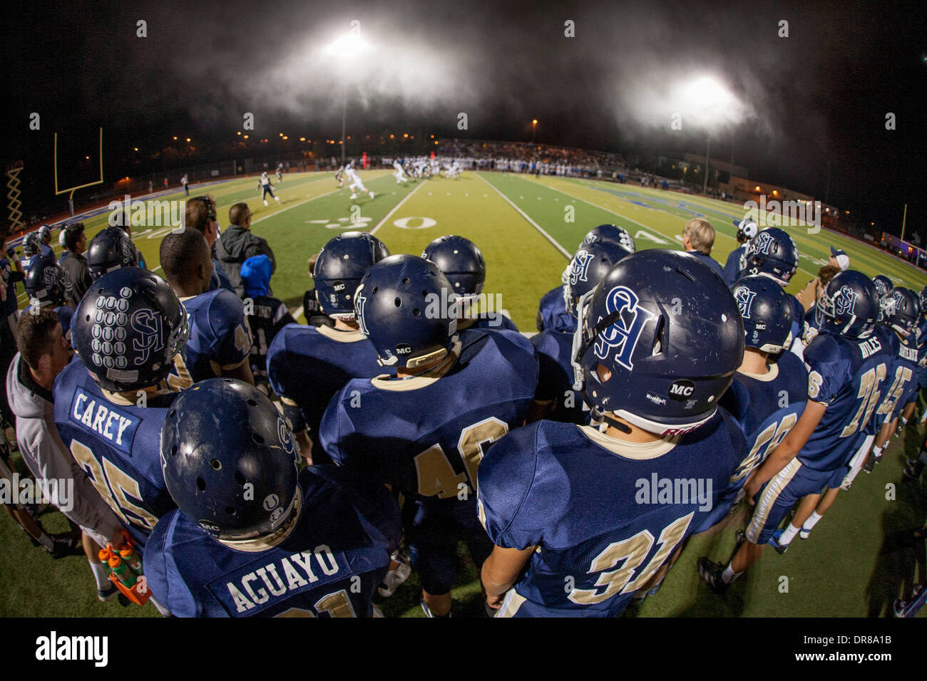 High school football players watch a night game from the sidelines in San Juan Capistrano, CA. - Stock Image