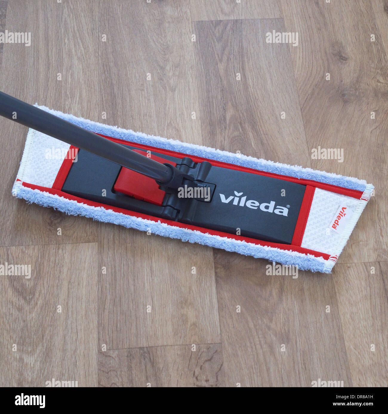 Vileda Mop Mopping a Beech Effect Vinyl Floor - Stock Image