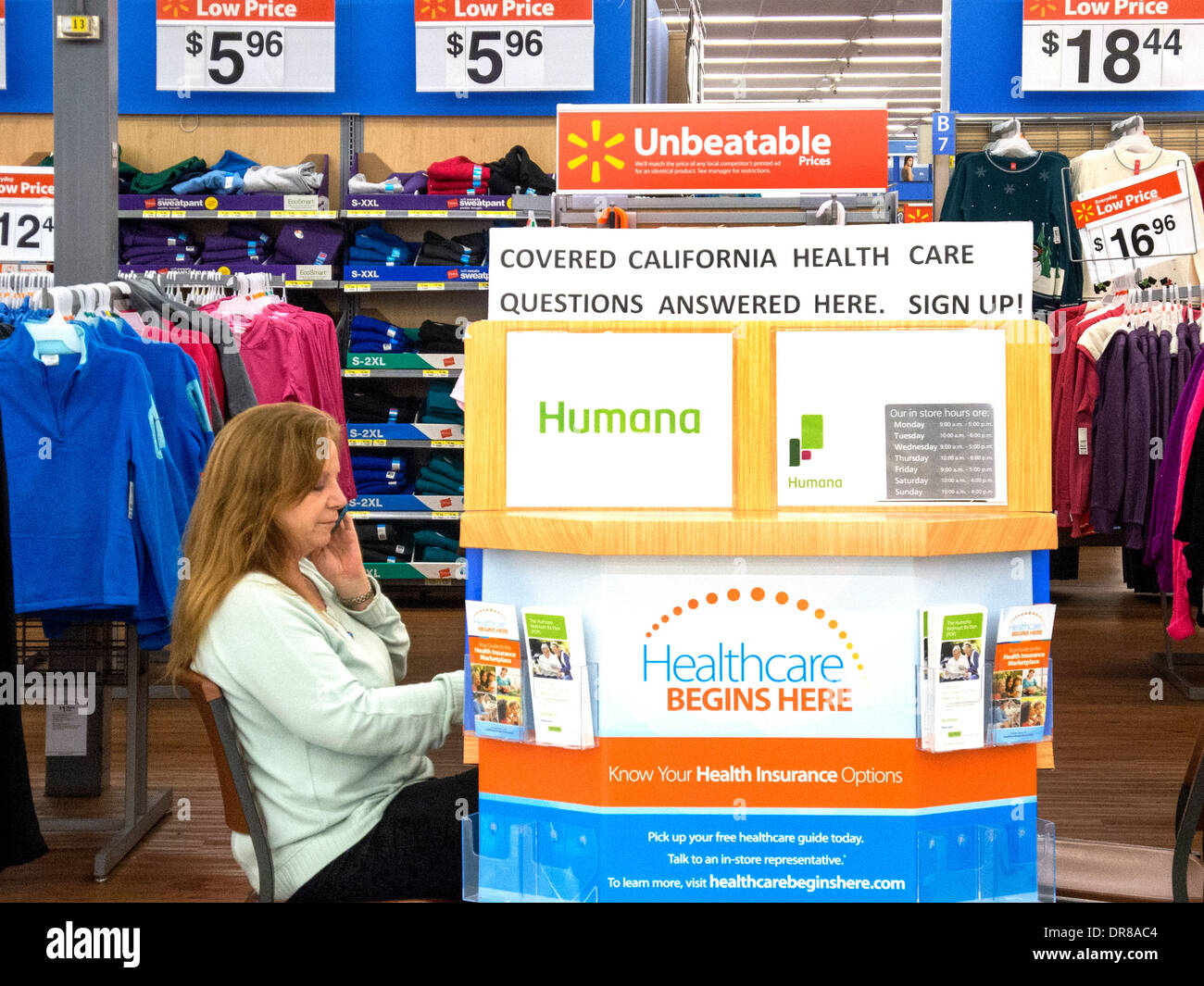 An insurance agent operates a sales kiosk at a Laguna Niguel, CA, discount clothing store offering coverage under the Affordable Healthcare Act or Obamacare, known in the state as Covered California. Note sign and brochures. - Stock Image