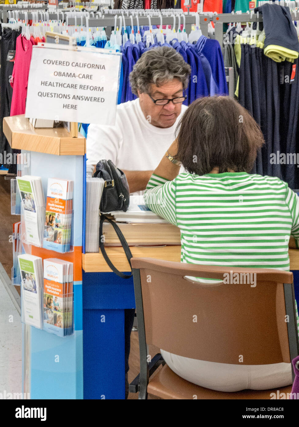 An insurance agent mans a sales kiosk at a Laguna Niguel, CA, discount clothing store offering coverage under the Affordable Healthcare Act or Obamacare, known in the state as Covered California. Note sign and brochures. - Stock Image