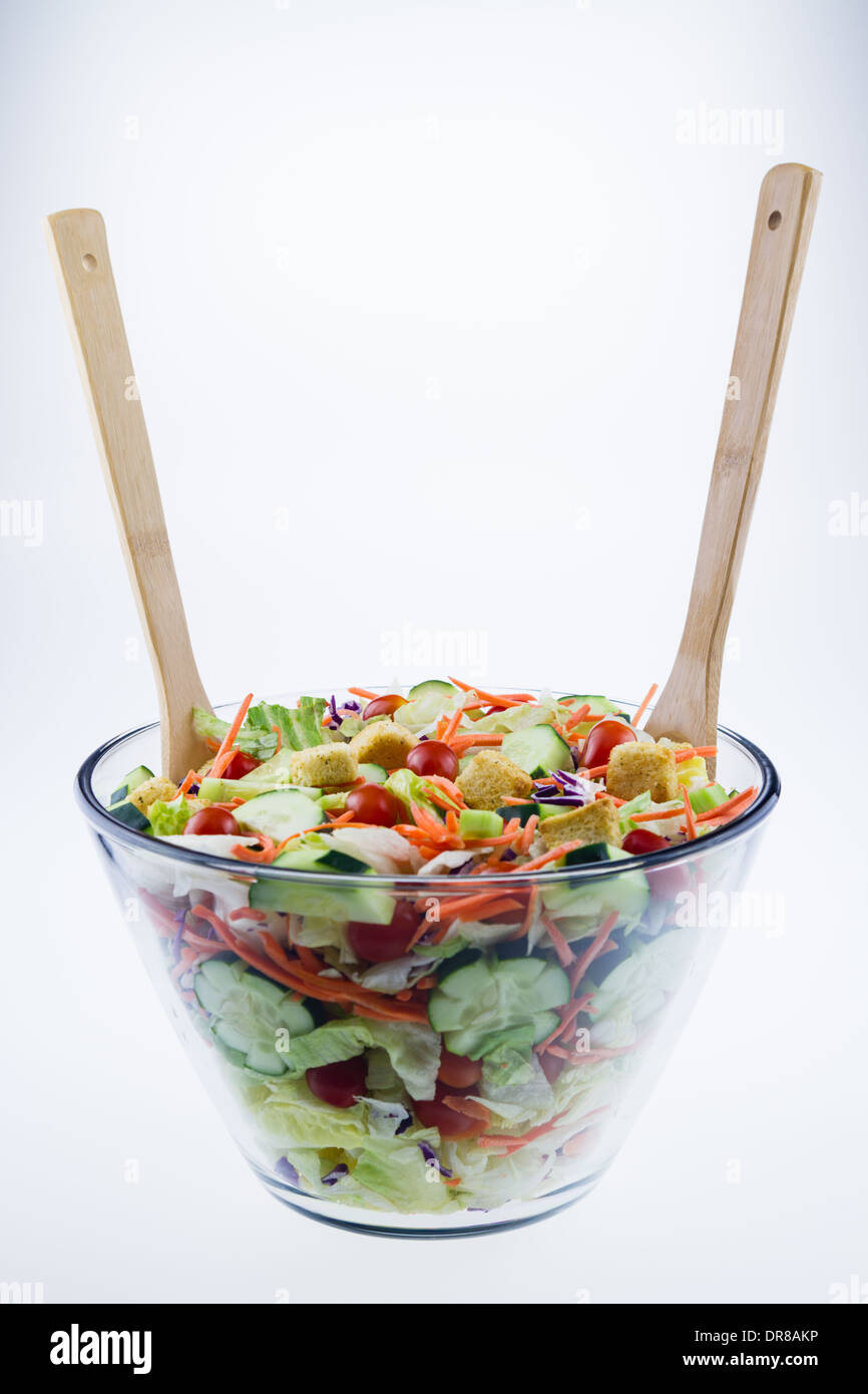 Fresh Tossed Garden Salad In A Glass Bowl With Wooden Spoons