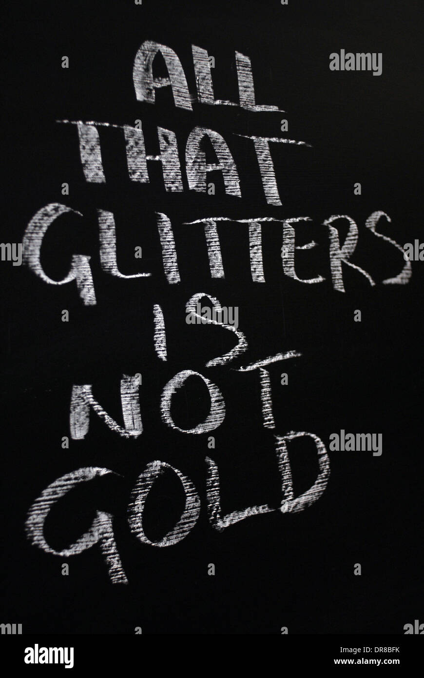 chalk writing- All that glitters is not gold.- words written on a blackboard. - Stock Image