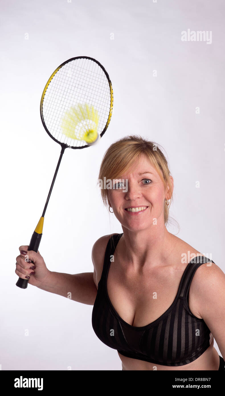 Badminton player wearing sports bra and lyrca shorts holding racquet - Stock Image